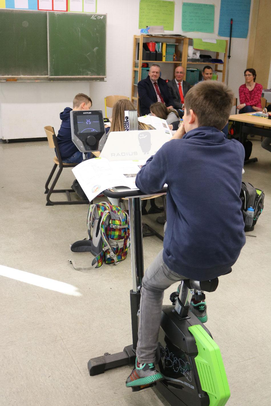 """Die Gäste (im Hintergrund) konnten sich bei der Einweihung in der Klasse 5a ein Bild davon machen, wie """"Bewegtes Lernen"""" in Arbeitsphasen funktioniert  Die Gäste (im Hintergrund) konnten sich bei der Einweihung in der Klasse 5a ein Bild davon machen, wie """"Bewegtes Lernen"""" in Arbeitsphasen funktioniert"""