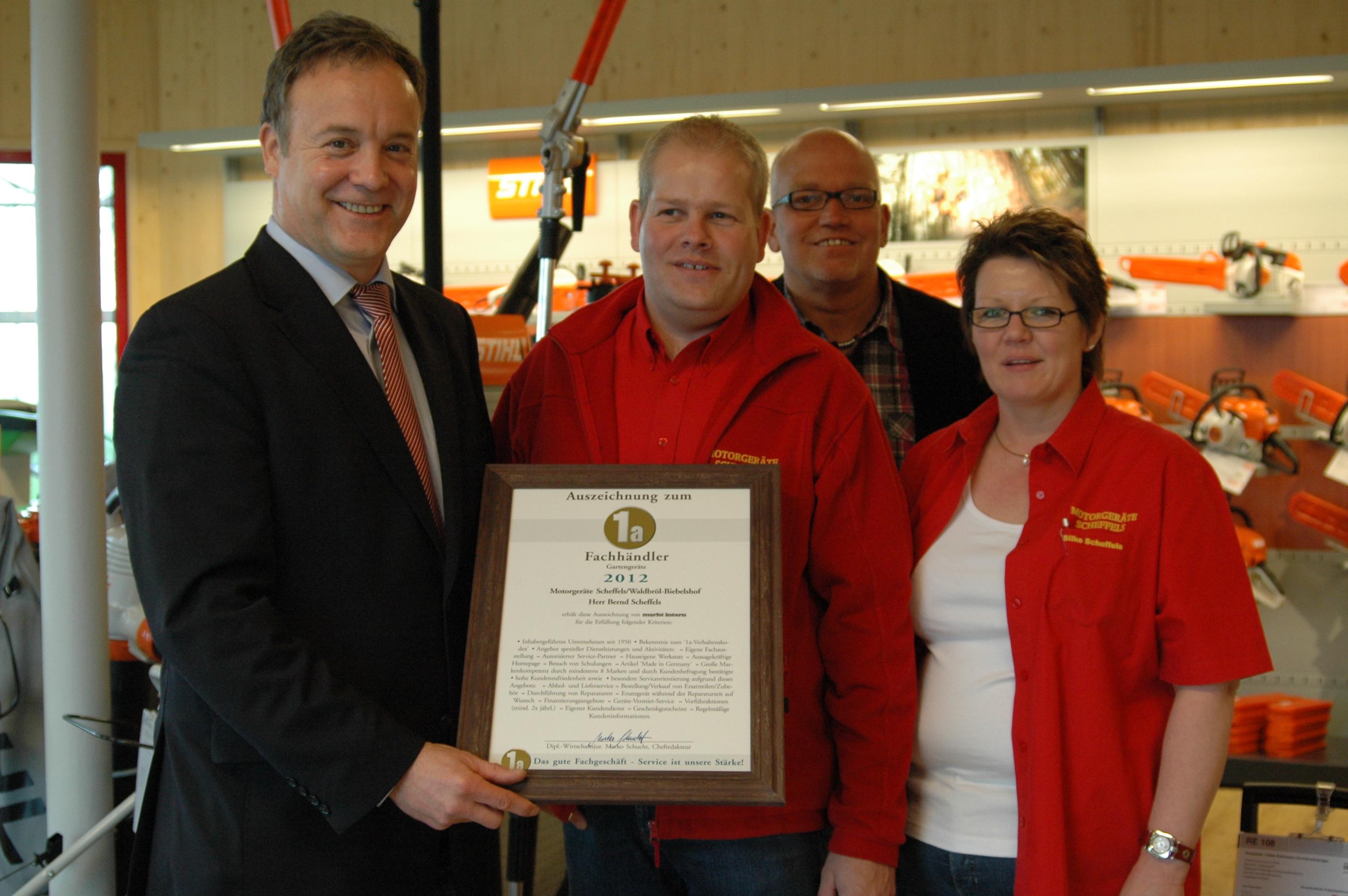 Bürgermeister Peter Koester und Wirtschaftsförderer Eckhard Becker gratulieren den Eheleuten Scheffels zur Auszeichnung 1a-Fachhändler