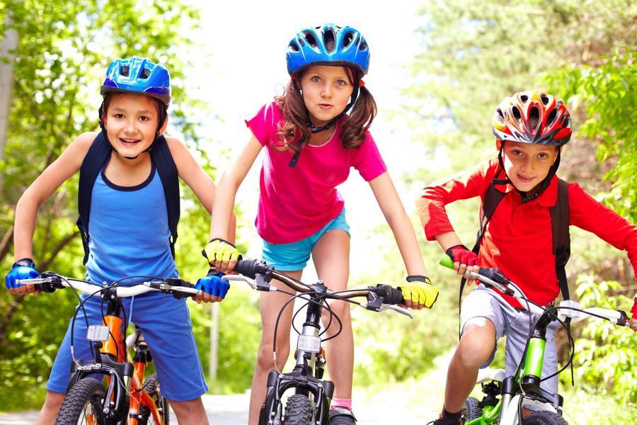 Auch dieses Jahr gibt es wieder eine Fahrradtour an der Sieg mit Eltern. Das Bild zeigt drei Kinder beim Fahrradfahren.