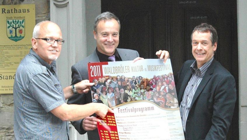 Eckhard Becker (Wir für Waldbröl GmbH), Peter Koester (Bürgermeister Stadt Waldbröl), Norbert Sell (Projektmanager) präsentieren das Plakat zum diesjährigen Waldbröler Kultur- und Musikfestival