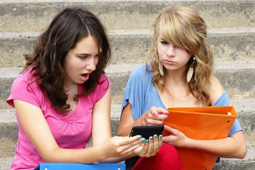 Symbolfoto zu Cybermobbing: Zwei Teenager mit einem Smartphone