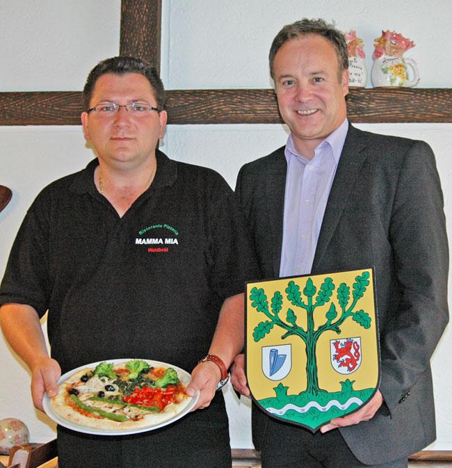 Catello Coppola und Bürgermeister Peter Koester präsentieren die Waldbröler Sommerpizza, die optisch dem Stadtwappen nachempfunden ist