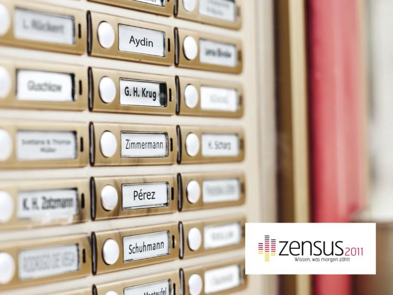 Wand mit zahlreichen Haustürklingeln und Namensschildern, darunter steht in der Ecke Zensus 2011 - Wissen was morgen zählt.