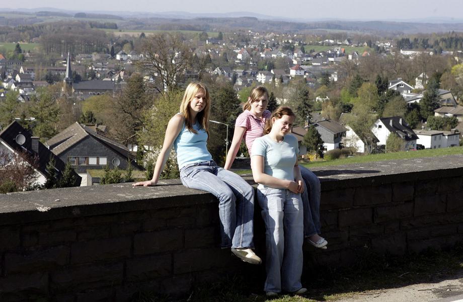 Jugendliche an der Mauer am Waldbröler Stadtrand, mit Blick über die Stadt