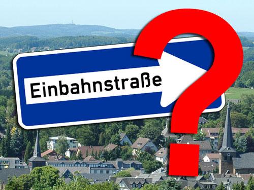 Illustration eines Einbahnstraßen-Schildes mit Fragezeichen vor einem Panoramablick über Waldbröl