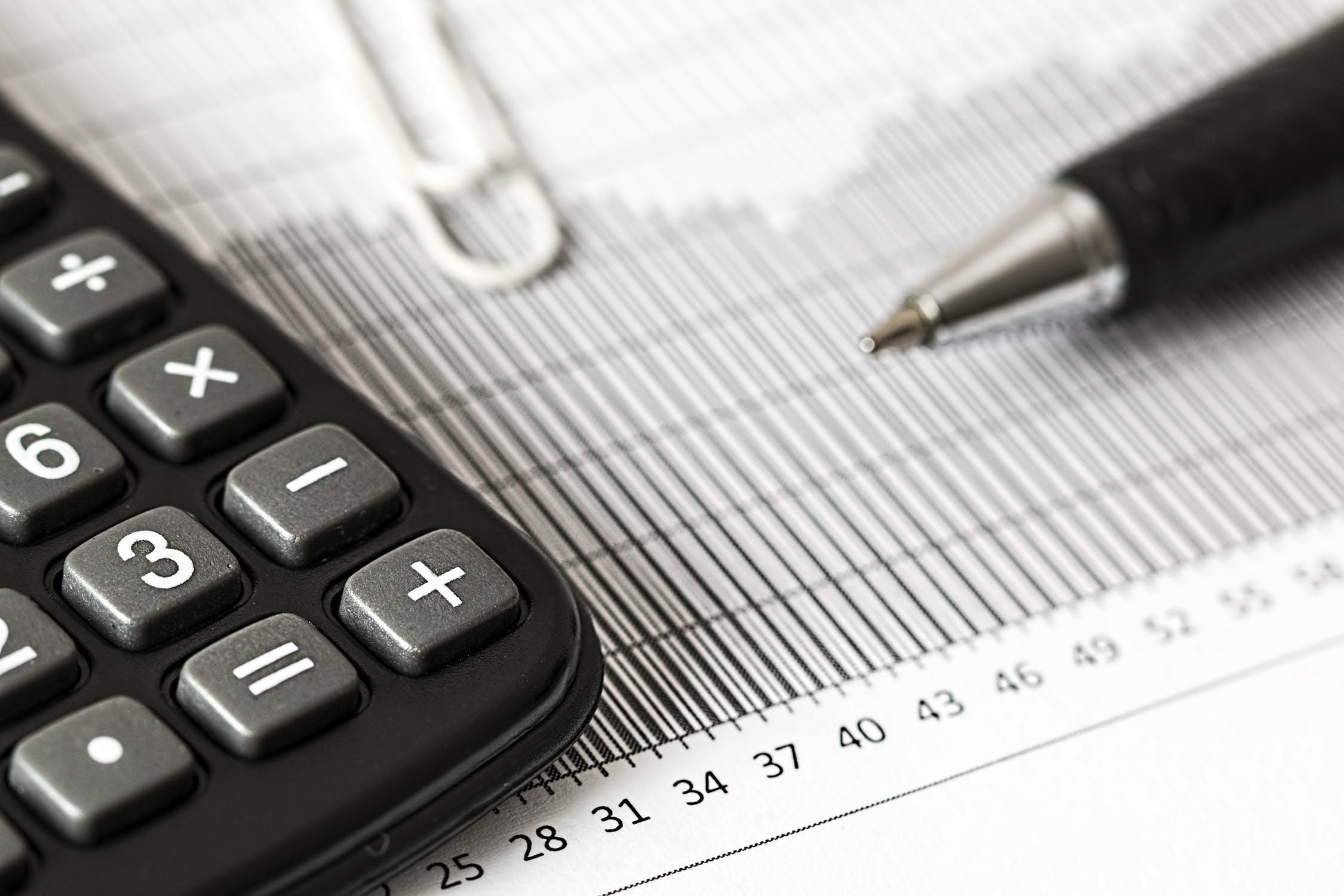 Symbolfoto Haushaltsplan: Taschenrechner und Stift