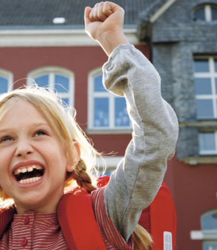 Das Bild zeigt ein lachendes Mädchen mit Schultournister vor einer Schule