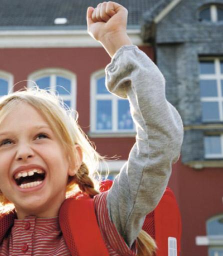Bild einer fröhlichen Grundschülerin vor einem Schulgebäude