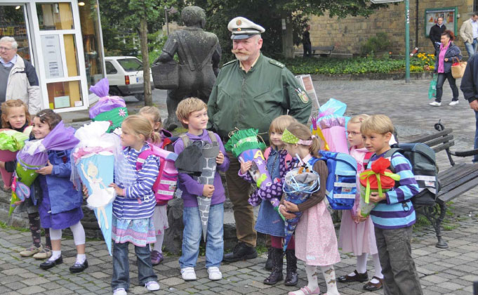 Ein Waldbröler Polizist in Uniform, umgeben von Schulkindern der ersten Klasse mit ihren Schultüten