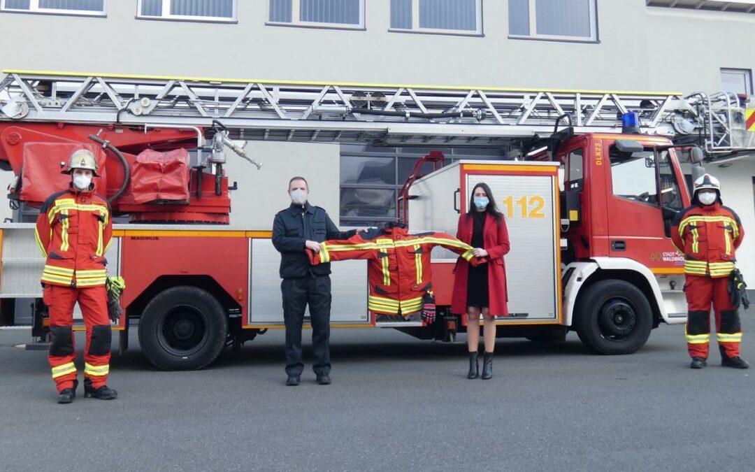 Foto: Bürgermeisterin Larissa Weber (2.v.r.) übergibt dem Leiter der Feuerwehr Daniel Wendeler (2.v.l.) die ersten Uniformen. Rechts und links zwei Kameraden in der neuen Uniform. Bildquelle: Feuerwehr Waldbröl